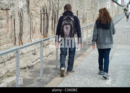 Touristen zu Fuß entlang eines erhaltenen Abschnitts der Berliner Mauer an der Topographie des Terrors-Freilichtmuseum - Stockfoto