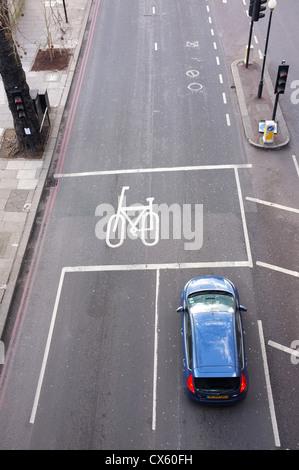 ein Auto hielt an der Ampel auf einer leeren Straße neben ein Radweg in London von oben genommen - Stockfoto