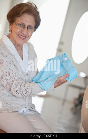 Eine ältere Frau mit einem Blue-Baby-t-Shirt - Stockfoto