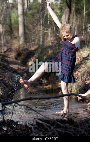 Mädchen treten ihre Füße durch das Wasser in Mooresville, North Carolina, USA - Stockfoto