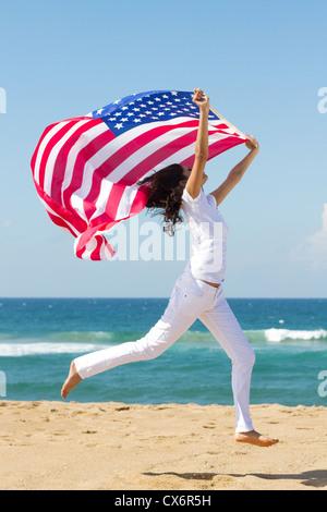 junge aktive Frau, die amerikanische Flagge und springen am Strand - Stockfoto