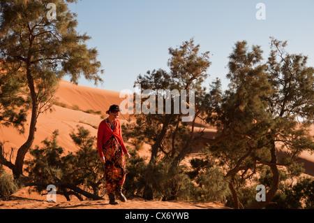 Ein Mädchen am oberen Rand einer Sanddüne in Marokko - Stockfoto
