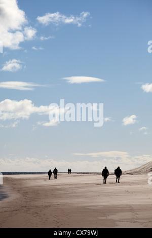 Drei Paare zu Fuß entlang der Sandstrand in der Nähe von Bamburgh Northumberland-Nord-Ost England UK - Stockfoto