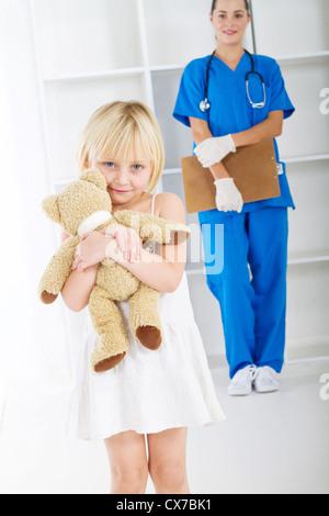 kleines Mädchen mit Teddybär in Arztpraxis - Stockfoto