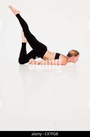 Eine Frau In einer Yoga-Pose; Tarifa, Cádiz, Andalusien, Spanien - Stockfoto