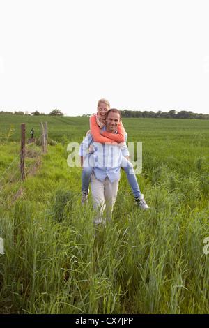Ein Mann seiner Freundin eine Huckepack Reiten durch ein Feld - Stockfoto