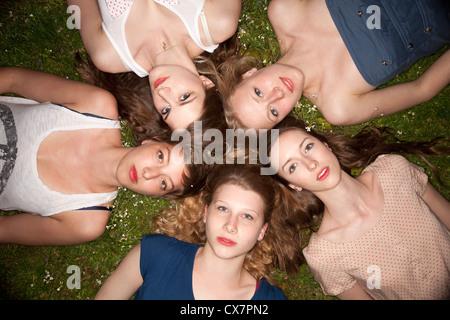 Fünf Freundinnen liegen in den Rasen in einem Kreis, sinnlich in die Kamera schaut - Stockfoto