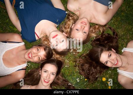 Fünf fröhliche Freundinnen in den Rasen, Kopf und Schultern liegend - Stockfoto