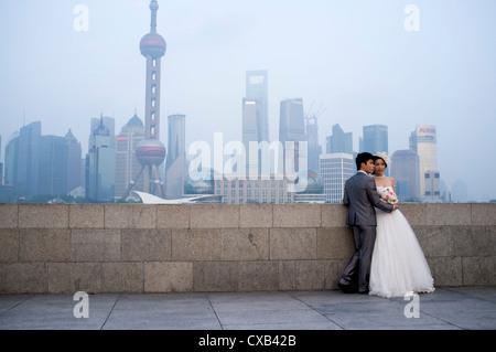 Jung verheiratet Paar posieren für Hochzeitsfotos am Bund mit Skyline von Pudong Finanzviertel hinten Shanghai China - Stockfoto