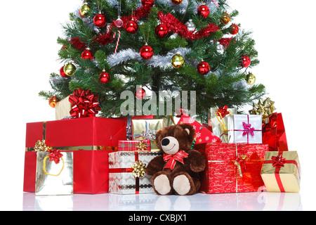 Geschmückter Weihnachtsbaum mit Kugeln und Lametta umgeben von Geschenk verpackt Geschenke und ein Teddybär - Stockfoto