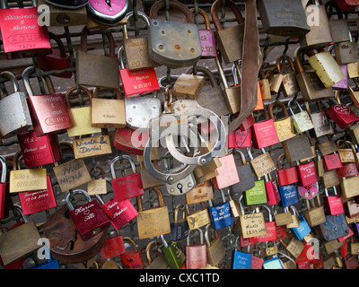 Vorhängeschlösser und Handschellen als Symbol für Beziehungen auf der Hohenzollernbrucke-Eisenbahnbrücke in Köln, - Stockfoto