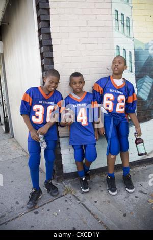 Drei junge Freunde & Teamkollegen in Uniform nach ihrer ersten Fußballspiel des Jahres. Brooklyn, NY. - Stockfoto