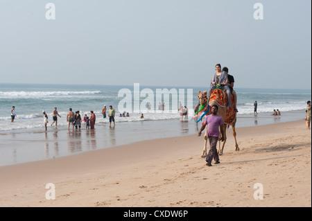 Indische Urlauber am Strand von Puri, junge Familien nehmen Kamelritt entlang dem Strand, Puri, Golf von Bengalen, - Stockfoto