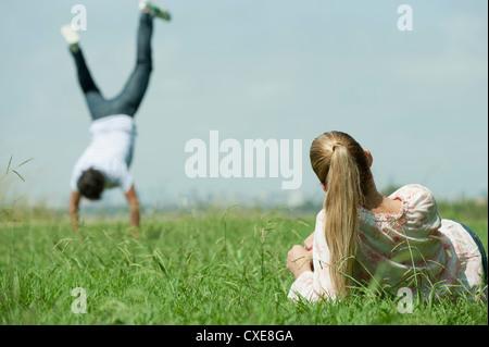 Frau liegend auf Rasen, beobachtete Man tun handstand - Stockfoto