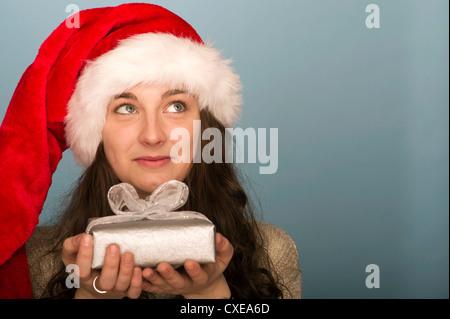Junge Frau mit Weihnachtsgeschenk, Nachschlagen in Gedanken - Stockfoto