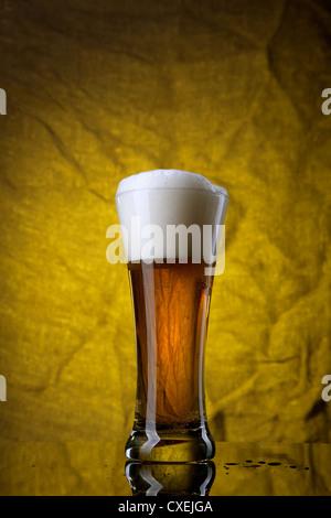 Bier im Glas auf gelben Hintergrund - Stockfoto