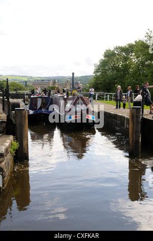 Zwei Narrowboats beenden die obere Kammer des Bingley fünf-Rise Schlösser an der Leeds and Liverpool Canal in Bingley, - Stockfoto