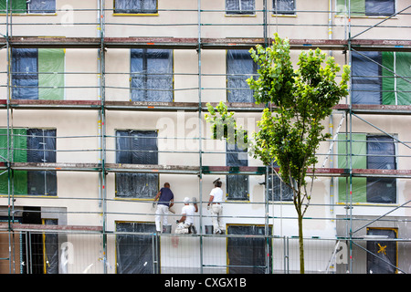 Arbeiter auf einem Gerüst, Verputzen der Wand eines neuen Wohnhauses. - Stockfoto