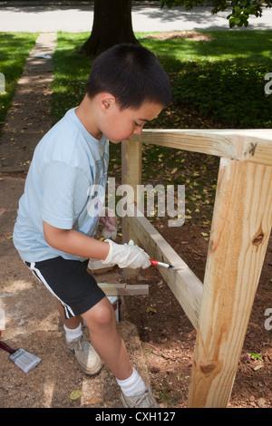 sechs Jahre alter Junge Malerei ein hölzerner Handlauf - Stockfoto