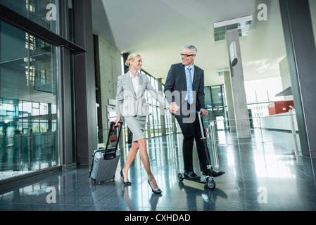 Deutschland, Stuttgart, Geschäftsfrau mit Rädern Gepäck, Mann Reiten Scooter im Bürogebäude - Stockfoto