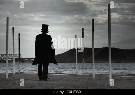 Rückansicht auf allein Mann im schwarzen Mantel und Hut gehen zum Strand. Natürliche Dunkelheit. Künstlerisch Farben - Stockfoto