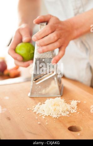Geriebenem Meerrettich auf ein Cuttingboard mit einem Koch Gitter Lime Peel im Hintergrund - Stockfoto