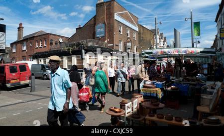 Menschen zu Fuß vorbei an Marktständen an der High Street in Walthamstow an einem sonnigen Sommertag in Walthamstow - Stockfoto