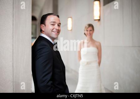 Porträt der Bräutigam mit der Braut im Hintergrund