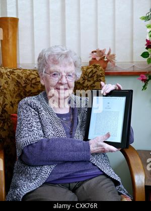 Glücklich und lächelnd 90 Jahre alten neunzigjährigen englische Rentner erfreut eine iPad als ihr Geburtstagsgeschenk - Stockfoto