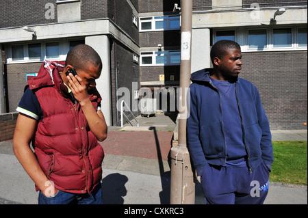 Zwei junge Arbeitslose Jugend Leeds UK, einer am Telefon sprechen. - Stockfoto
