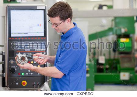 Techniker messen Zahnrad mit Vernier Bremssattel vor Schneidemaschine Drehbank in Hightech-Produktionsanlage - Stockfoto