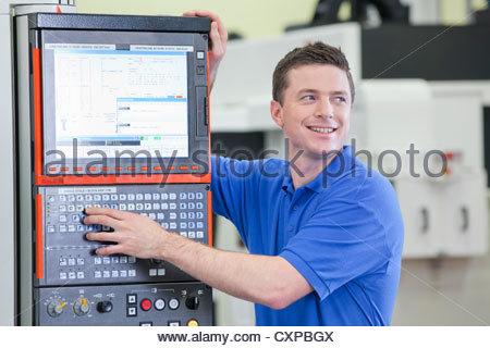Lächelnd Techniker controlling Drehbank-Schneidemaschine in Hightech-Produktionsanlage - Stockfoto