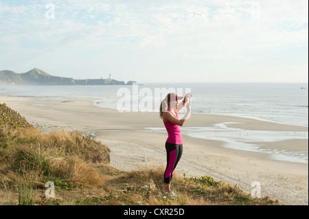Aktive junge Frau nehmen Foto am Strand - Stockfoto