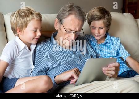 Großvater und Enkel Blick auf digital-Tablette - Stockfoto