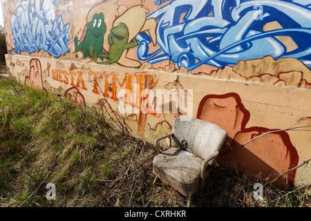 Siesta-Sitz auf einer Brachfläche, zerschlissenen Sessel, Graffitiwand, stillgelegten umschalten Hof Bahnhof Duisburg - Stockfoto