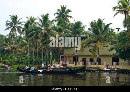 Horizontale Ansicht einer kleinen Fabrik mit Arbeitern in Booten hochziehen zum Be- und Entladen von Fracht entlang - Stockfoto