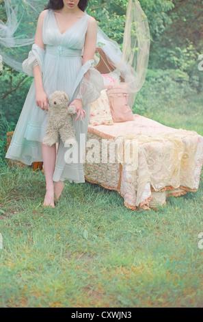 Aufnahme einer blass junge Frau trägt ein schickes blau Nachthemd im Wald und hält ein Teddybär neben einem Kinderbett - Stockfoto