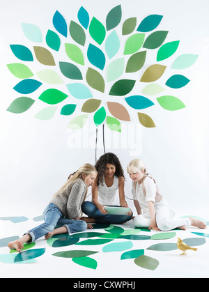 Mädchen reden unter Baum an Wand - Stockfoto