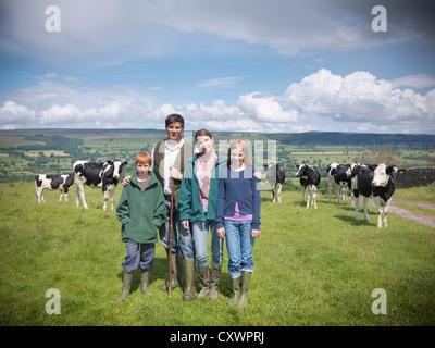 Landwirt posiert mit Familie im Feld - Stockfoto