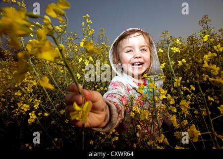 Lächelndes Mädchen spielen im Bereich der Blumen - Stockfoto