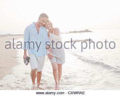 Paare, die in Wellen am Strand - Stockfoto