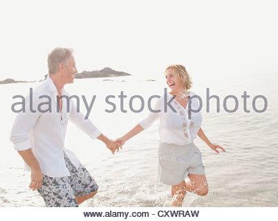 Paar spielen in Wellen am Strand - Stockfoto