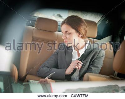 Geschäftsfrau im Rücksitz Auto schreiben - Stockfoto