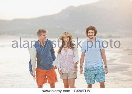 Freunde, die zusammen am Strand spazieren - Stockfoto