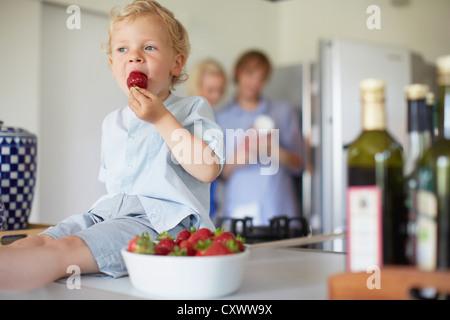 Junge, Essen Erdbeeren am Zähler - Stockfoto