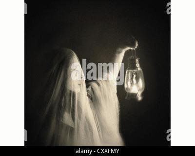 Eine gespenstische Frau, verhüllt in weiß, hält eine Laterne Nd betrachten. - Stockfoto