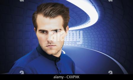 Junger Mann stand vor einem beleuchteten Tunnel, futuristischen Szene, ernstem Gesicht - Stockfoto
