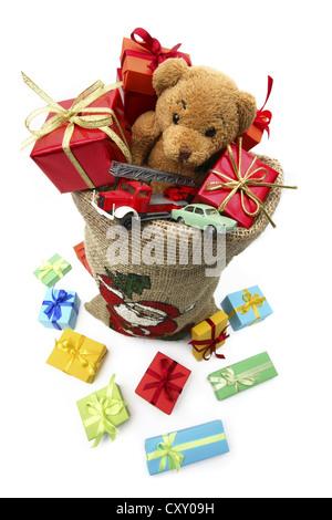 Christms Sack voller Weihnachten Geschenke, ein Teddybär und Spielzeugautos - Stockfoto