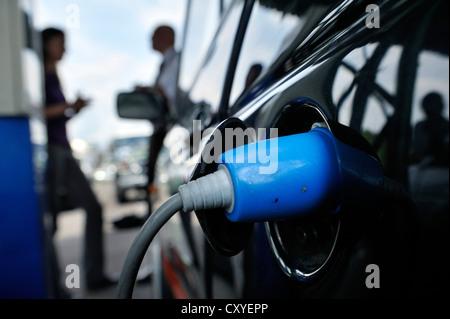Elektro-Auto wird an einer Steckdose aufgeladen - Stockfoto