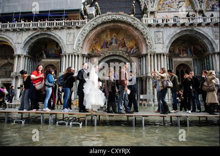 """Ein verheiratetes Paar Spaziergang vor der Markusdom am ersten Tag der Saison """"Acqua Alta"""" in Venedig. - Stockfoto"""